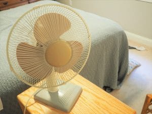 fan next to a bed