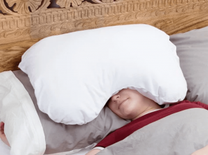man sleeping with pillow over his head