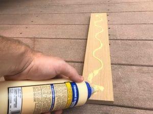 applying wood glue to a board